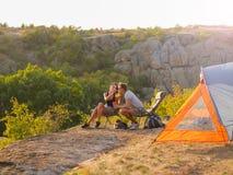 Uomo e donna che mangiano su uno sfondo naturale Una coppia che gode di bella vista Accampandosi, concetto di viaggio Copi lo spa Fotografie Stock Libere da Diritti