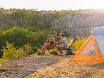 Uomo e donna che mangiano su uno sfondo naturale Una coppia che gode di bella vista Accampandosi, concetto di viaggio Copi lo spa Immagine Stock Libera da Diritti