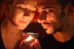 Uomo e donna che mantengono candela e sguardo di vetro Fotografia Stock