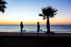 Uomo e donna che pareggiano sul lungonmare che fa forma fisica di mattina Fotografia Stock Libera da Diritti