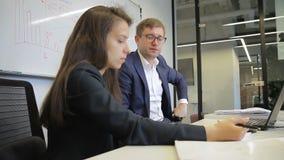 Uomo e donna che parlano mentre prendendo le note in ufficio moderno archivi video