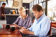 Uomo e donna che per mezzo degli Smart Phone alla caffetteria immagine stock libera da diritti