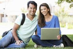 Uomo e donna che per mezzo del computer portatile all'aperto Fotografie Stock Libere da Diritti