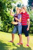 Uomo e donna che raccolgono le mele dall'albero Immagine Stock Libera da Diritti
