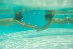 Uomo e donna che raggiungono fuori per a vicenda sotto l'acqua Fotografia Stock