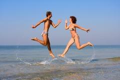 Uomo e donna che saltano nel mare Fotografia Stock
