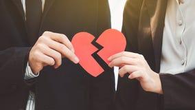 Uomo e donna che separano un cuore di carta rosso Il concetto dell'ONU Fotografia Stock Libera da Diritti