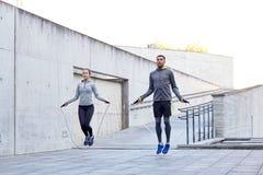 Uomo e donna che si esercitano con la salto-corda all'aperto Fotografia Stock