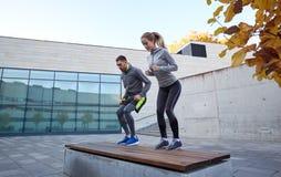 Uomo e donna che si esercitano sul banco all'aperto Immagine Stock Libera da Diritti