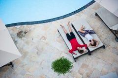 Uomo e donna che si rilassano sui lettini Immagini Stock