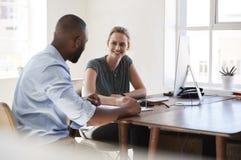 Uomo e donna che si siedono ad uno scrittorio che parla in un sorridere dell'ufficio Fotografia Stock