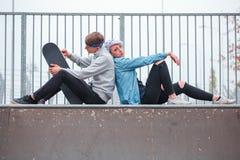 Uomo e donna che si siedono su una superficie lunga con un pattino fotografia stock