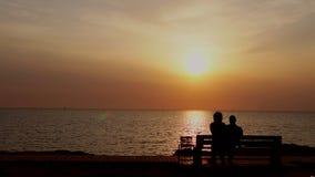 Uomo e donna che si siedono sul banco che guarda il tramonto sul mare video d archivio