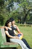 Uomo e donna che si siedono sulla pallavolo della holding del banco Immagini Stock Libere da Diritti