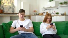 Uomo e donna che si trascurano in loro telefoni cellulari nella loro casa nel corso della mattinata Le coppie antisociali trascur stock footage