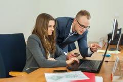 Uomo e donna che spendono tempo nell'ufficio Donna che si siede dietro Fotografia Stock