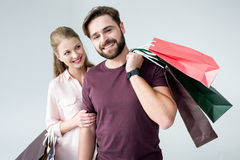 Uomo e donna che stanno con i sacchetti della spesa e sorridere fotografia stock libera da diritti