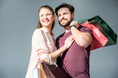 Uomo e donna che stanno con i sacchetti della spesa e sorridere fotografia stock