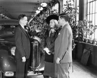 Uomo e donna che stanno in una sala d'esposizione dell'automobile che parla con rappresentante (tutte le persone rappresentate no Fotografia Stock Libera da Diritti
