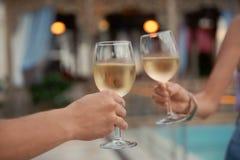 Uomo e donna che tengono i vetri di vino bianco Immagini Stock