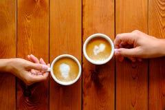 Uomo e donna che tengono una tazza di caffè in un caffè, vista superiore Immagini Stock Libere da Diritti
