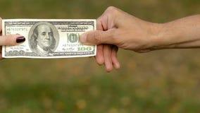 Uomo e donna che tirano i lati di una banconota in dollari stock footage