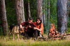 Uomo e donna che viaggiano con il cane al campo Fotografia Stock Libera da Diritti