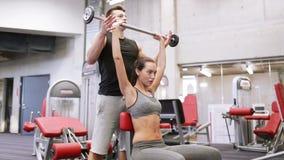 Uomo e donna con il bilanciere che flette i muscoli in palestra stock footage