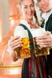 Uomo e donna con il vetro di birra in fabbrica di birra Fotografia Stock