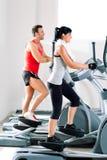 Uomo e donna con l'addestratore trasversale ellittico a ginnastica Immagini Stock Libere da Diritti