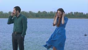 Uomo e donna con la conversazione dei telefoni cellulari archivi video