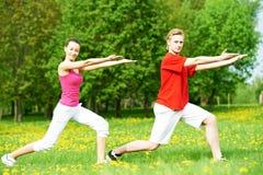 Uomo e donna di forma fisica che fanno allungando gli esercizi Fotografia Stock Libera da Diritti