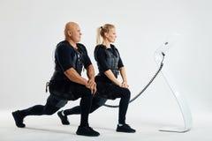 Uomo e donna di misura che allungano le gambe all'interno che fanno affondo di andata fotografia stock libera da diritti