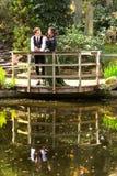Uomo e donna di modo vittoriano vicino al lago con le riflessioni in parco Fotografie Stock Libere da Diritti