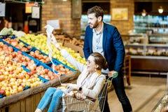 Uomo e donna divertendosi durante l'acquisto nel supermercato fotografia stock