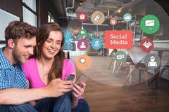Uomo e donna felici che per mezzo del telefono cellulare dai grafici sociali di media Fotografia Stock Libera da Diritti