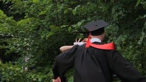 Uomo e donna felici in vestiti accademici che ballano nel parco, graduation stock footage