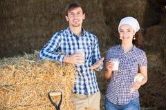 Uomo e donna in fieno con latte Immagine Stock Libera da Diritti