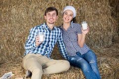 Uomo e donna in fieno con latte Immagine Stock