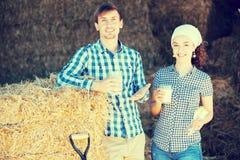Uomo e donna in fieno con latte Fotografia Stock Libera da Diritti