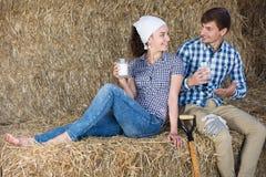 Uomo e donna in fieno con latte Fotografia Stock