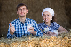 Uomo e donna in fieno con latte Immagini Stock Libere da Diritti