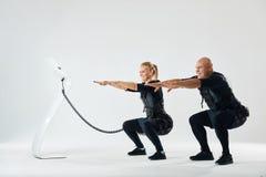 Uomo e donna nei vestiti di SME che sviluppano forza del centro immagine stock