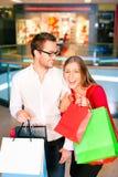 Uomo e donna nel centro commerciale con i sacchetti Fotografia Stock Libera da Diritti
