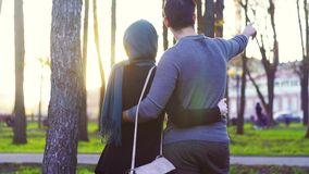 Uomo e donna nel hijab che abbraccia nel parco stock footage
