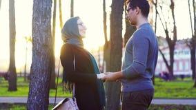 Uomo e donna nel hijab che si tengono per mano nel parco video d archivio
