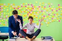 Uomo e donna nell'ufficio con molte priorità contrastanti dentro Immagini Stock