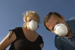 Uomo e donna nelle mascherine Fotografia Stock