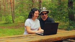 Uomo e donna in parco sul banco che lavora con il computer portatile stock footage
