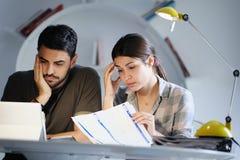 Uomo e donna preoccupati per le tasse ed il bilancio familiare Immagine Stock